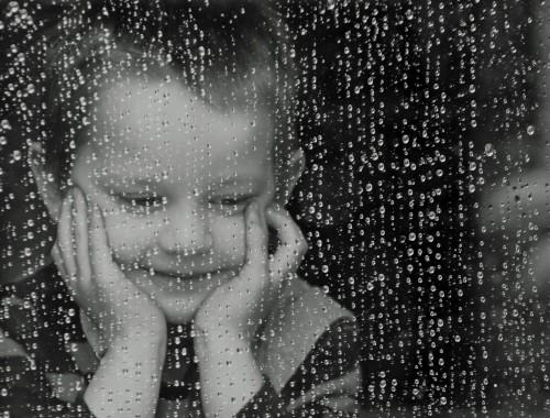 enfant souriant derrière une vitre couverte de gouttes de pluie